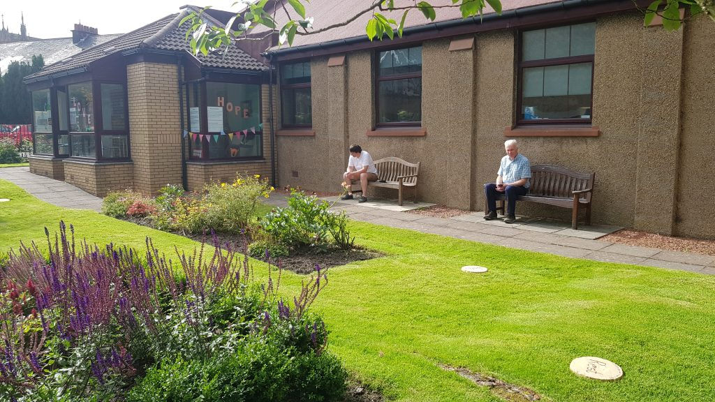 Church garden from Kildary Road with two people sat on the benches