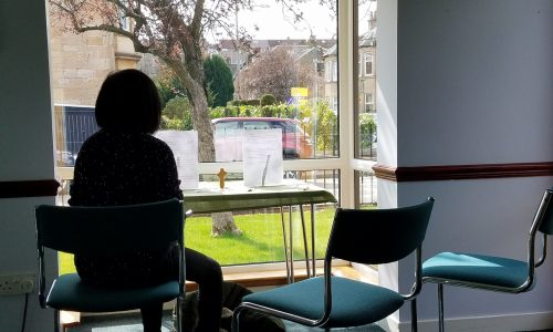 Person sat in chair facing window at prayer station in Fellowship Lounge