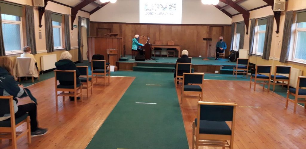 Socially distanced Wednesday morning service from back of sanctuary